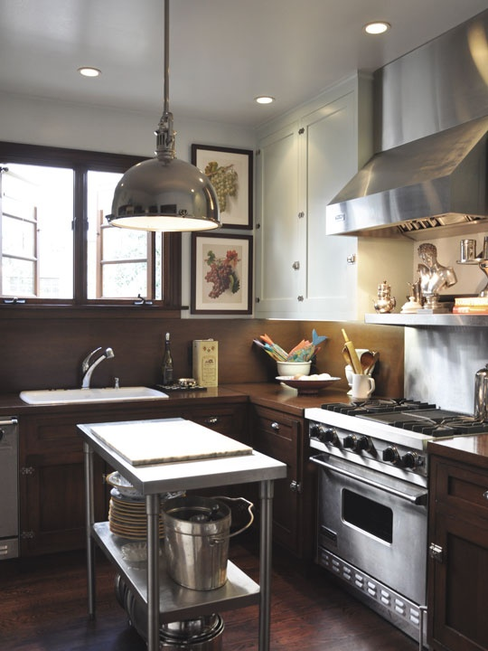 Industrial elements from steel counter tops to lighting and small islands-image via Apartment Therapy